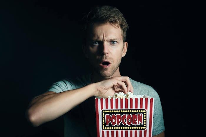 A man eating popcorn and watching a movie he purchased from That Movie Site after getting huge movie deals.